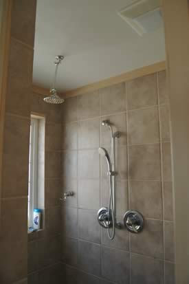 master bathroom features a large, tiled walk-in shower w/rainfall showerhead