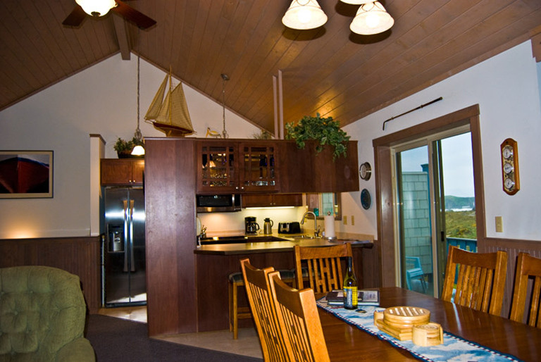 Pass thru kitchen with 3 bar stools and dining